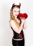 Young and beautiful curly girl with red horns looks like pretty Devil, holding a heart pillow Royalty Free Stock Images
