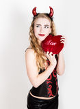 Young and beautiful curly girl with red horns looks like pretty Devil, holding a heart pillow Stock Photo