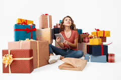 Young beautiful curly girl sitting on floor among gift boxes with just opened present tablet Isolated Royalty Free Stock Images
