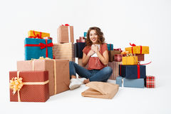 Young beautiful curly girl sitting on floor among gift boxes with just opened present tablet Isolated Royalty Free Stock Image