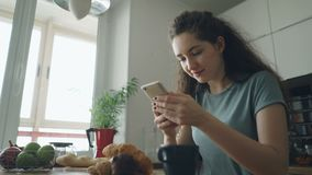 Young beautiful curly pretty caucasian woman sitting at table in nice kitchen using smartphone, she is texting someone. Young beautiful curly pretty caucasian stock video