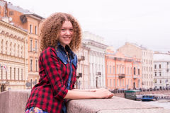 Young beautiful curly teen girl coquettishly smiles while standing on the Moika River in St. Petersburg, Russia Stock Images