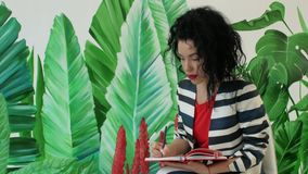 Young, beautiful curly woman makes notes in a notebook stock footage