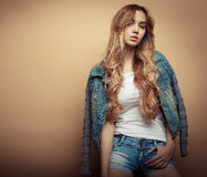 Young beautiful curly woman posing  over yellow background Royalty Free Stock Image