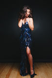 Young beautiful curly women in glitter dress on dark background. Copyspace. Concept celebration. Young beautiful curly woman in glitter dress on dark background Stock Photos