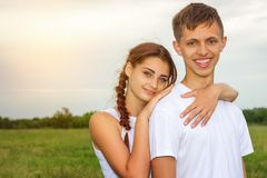 Young beautiful cute couple girl and guy are standing arm in arm on a background of nature, the concept of the relationship royalty free stock photos