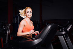 Young beautiful cute girl in fitness model in the gym running on the treadmill with bottle Royalty Free Stock Photos