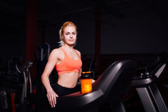 Young beautiful cute girl in fitness model in the gym running on the treadmill with bottle Stock Photography