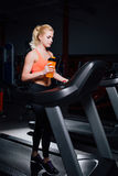 Young beautiful cute girl in fitness model in the gym running on the treadmill with bottle Royalty Free Stock Photography