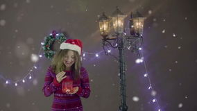 Young beautiful cute girl smiling wearing Santa hat, holding lantern in hand on background of Christmas decorations stock video