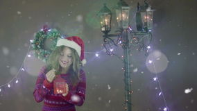 Young beautiful cute girl smiling wearing Santa hat, holding lantern in hand on background of Christmas decorations stock footage