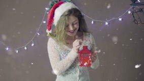 Young beautiful cute girl smiling wearing Santa hat, holding lantern in hand on background of Christmas decorations stock video footage