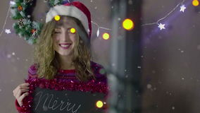Young beautiful cute girl smiling wearing Santa hat, holding a small chalkboard with inscription Merry Chistmas in hand stock footage