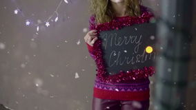 Young beautiful cute girl smiling wearing Santa hat, holding a small chalkboard with inscription Merry Chistmas in hand stock video