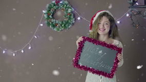 Young beautiful cute girl smiling wearing Santa hat, holding a small chalkboard with inscription Merry Chistmas in hand stock video footage