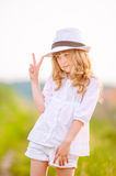 Young beautiful cutie posing in a hat near the field. The young beautiful cutie posing in a hat near the field royalty free stock photos