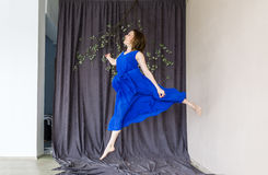 Young beautiful dancer in blue dress posing on a dance shool background.  Stock Photos