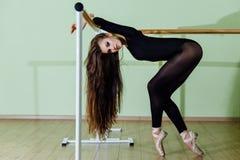 Young beautiful dancer posing in studio wit Ballet bar on tiptoe. Modern sexy brunette. Young beautiful dancer posing in studio wit Ballet bar on tiptoe. Modern Royalty Free Stock Photos