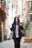 Italian girl on in the streets. A young beautiful dark hair woman with a handbag and boats walking with intent in the beautiful narrow streets of Genoa, an old stock photos