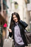 Happy girl with lollipop. A young beautiful dark hair woman with a handbag and boats walking with intent in the beautiful narrow streets of Genoa, an old Italian stock images