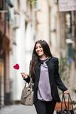 Happy girl with lollipop. A young beautiful dark hair woman with a handbag and boats walking with intent in the beautiful narrow streets of Genoa, an old Italian royalty free stock image