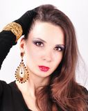 Young beautiful  dark-haired girl in extravagant earrings Royalty Free Stock Photos