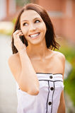 Young beautiful dark-haired woman. In white dress laughs and talks on cellular telephone, against city landscape Royalty Free Stock Photos