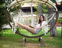 Young beautiful dark-haired woman in hammock with laptop in gard Stock Photography