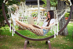 Young beautiful dark-haired woman in hammock with laptop Royalty Free Stock Photos