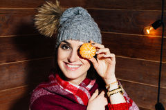 Young beautiful dark-haired woman smiling in winter clothes and cap with tangerines on wooden background. Young beautiful dark-haired woman smiling in winter Stock Photos