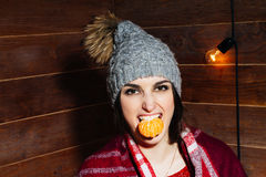 Young beautiful dark-haired woman smiling in winter clothes and cap with tangerines on wooden background. Royalty Free Stock Photos