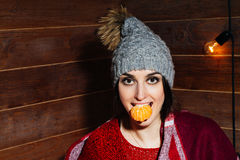 Young beautiful dark-haired woman smiling in winter clothes and cap with tangerines on wooden background. Royalty Free Stock Photography