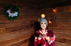 Young beautiful dark-haired woman smiling in winter clothes and cap with tangerines on wooden background. Young beautiful dark-haired woman smiling in winter Royalty Free Stock Images