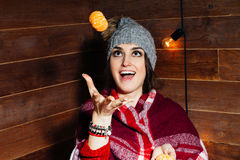 Young beautiful dark-haired woman smiling in winter clothes and cap with tangerines on wooden background. Young beautiful dark-haired woman smiling in winter Royalty Free Stock Photography