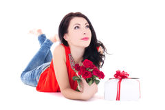 Young beautiful daydreaming woman lying with gift box and flower Stock Photo
