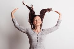 A young beautiful delighted woman in studio with hands and hair in the air. royalty free stock photos