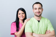 Young and beautiful dental doctors. Posing on gray background royalty free stock image
