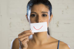 Young beautiful depressed woman hiding her sorrow and sadness behind a paper with a drawn smile Stock Photos