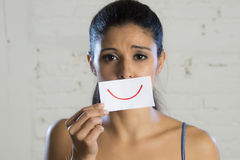 Young beautiful depressed woman hiding her sorrow and sadness behind a paper with a drawn smile Royalty Free Stock Photos