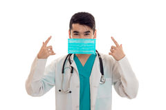 Young beautiful doctor in blue uniform and mask with stethoscope on his neck isolated on white background Royalty Free Stock Photography