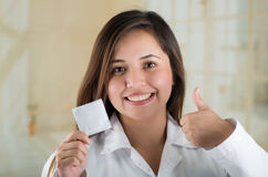 Young beautiful doctor holding a condom package and doing with her hand a thumb up, safe sex concept. Protection against Stock Image