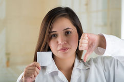 Young beautiful doctor holding a male condom package and doing with her hand a thumbs down, safe sex concept. Protection Stock Images
