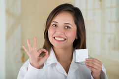 Young beautiful doctor holding a male condom package and doing a ok signal with her hand, safe sex concept. Protection Stock Photo