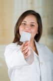 Young beautiful doctor pointing in from of her face a condom package, protection, safe sex concept. Protection against Stock Image