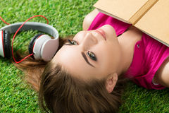 Young beautiful dreamy woman laying on grass in the park Stock Photos