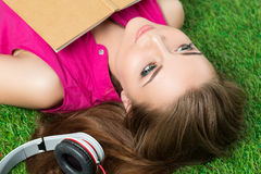 Young beautiful dreamy woman laying on grass in the park Royalty Free Stock Images