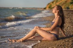 Dreamy woman sits in the sea surf. Young beautiful dreamy woman with long brown hair in ornamented swimsuit sits on wild pebbly beach in the sea surf at the Stock Photography