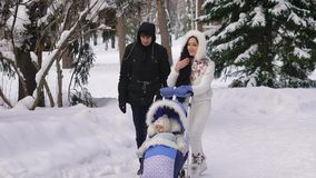 Young beautiful dressed parents walking on snow-covered park with your child sitting in the baby carriage by ski stock video footage