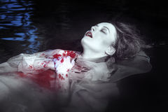 Young beautiful drowned woman in bloody dress. Lying in the water outdoor royalty free stock image