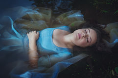Young beautiful drowned woman in blue dress lying in the river. Young beautiful drowned woman in blue dress lying in the water outdoor royalty free stock images